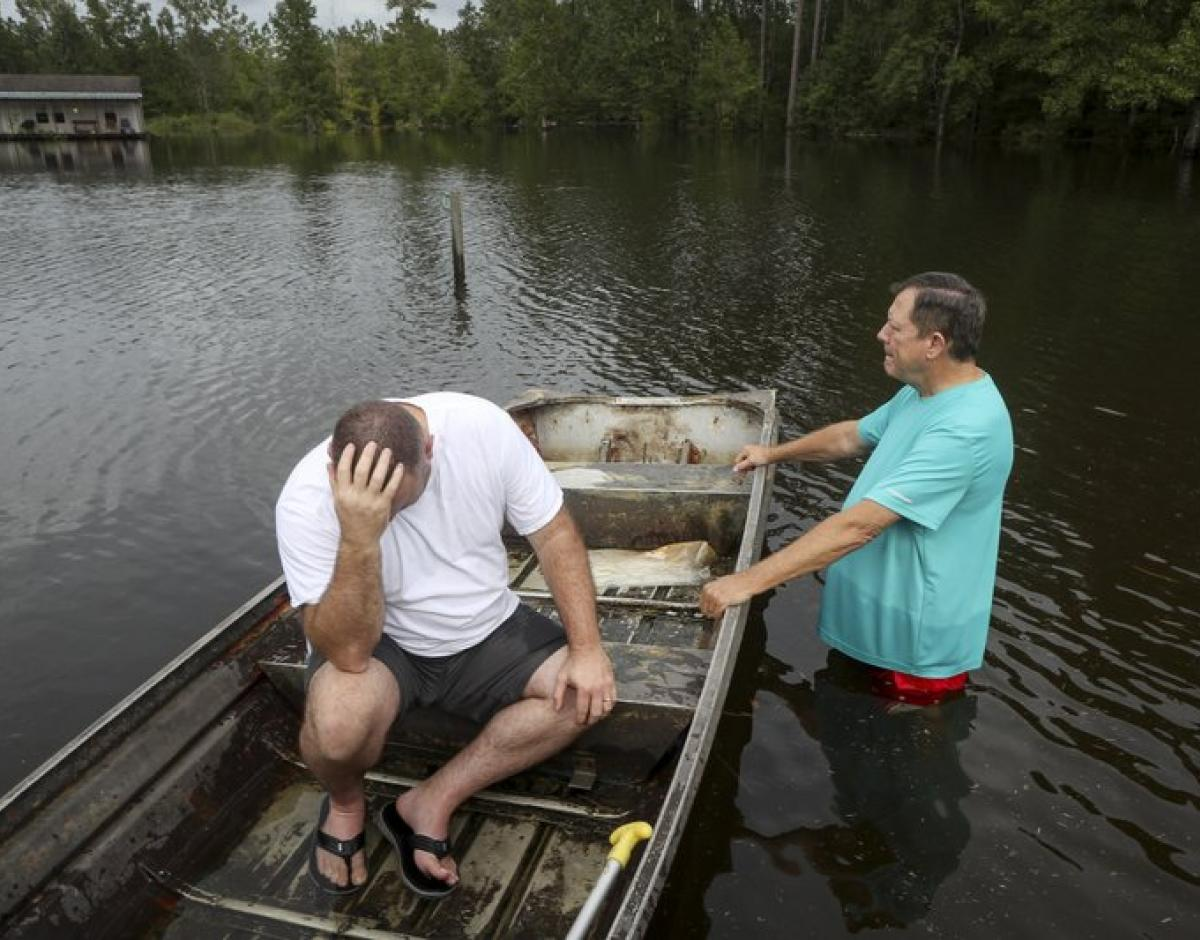 A man sits in a boat floating on flood waters beside another man.