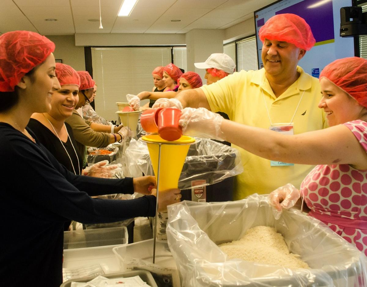 Global Impact employees participate in a food packing event.