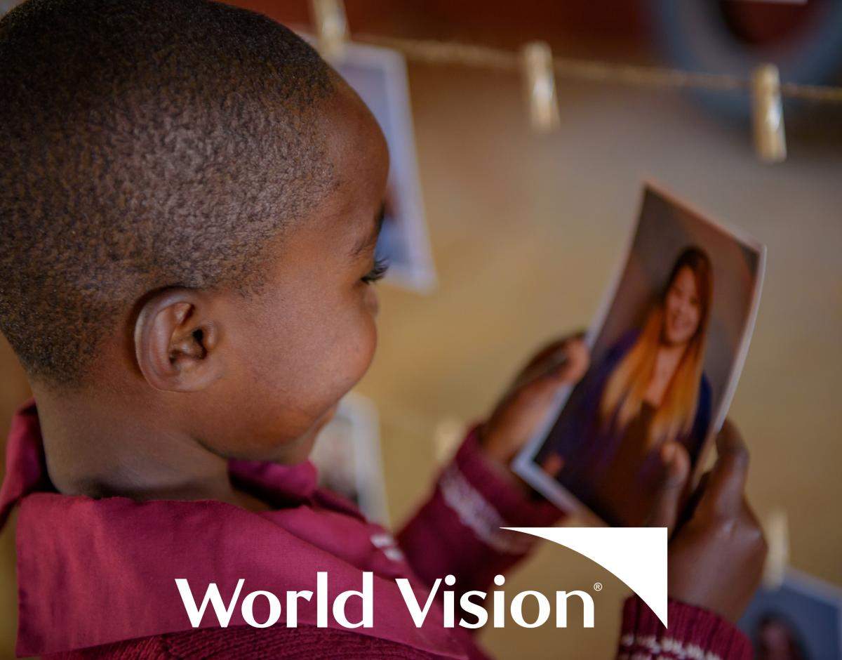 A child looks at her sponsor's photo