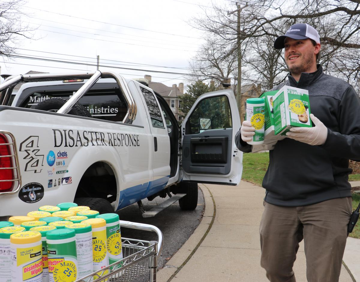 A man gathers supplies for Matthew 25: Ministries coronavirus response efforts.