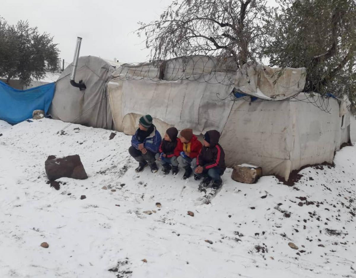 Child refugees sit in the snow.