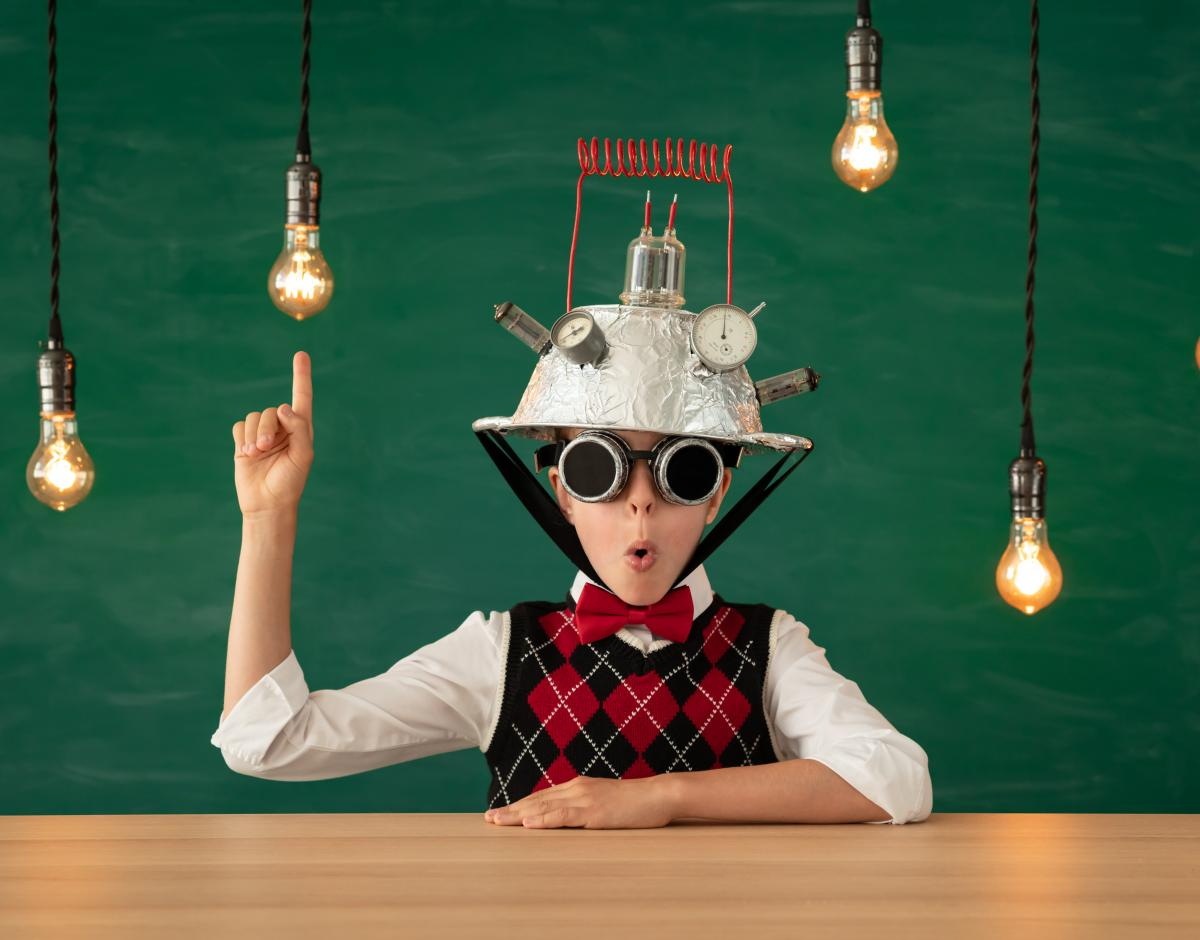 Child wearing a tinfoil hat and glasses, pointing up at light bulbs handing from above.