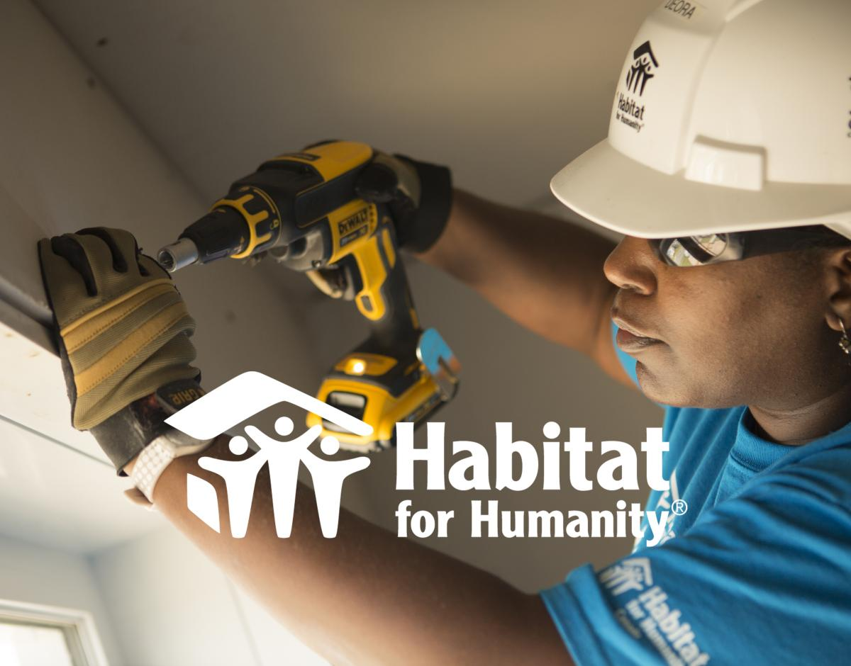 A Habitat for Humanity International worker uses a drill inside of a house.