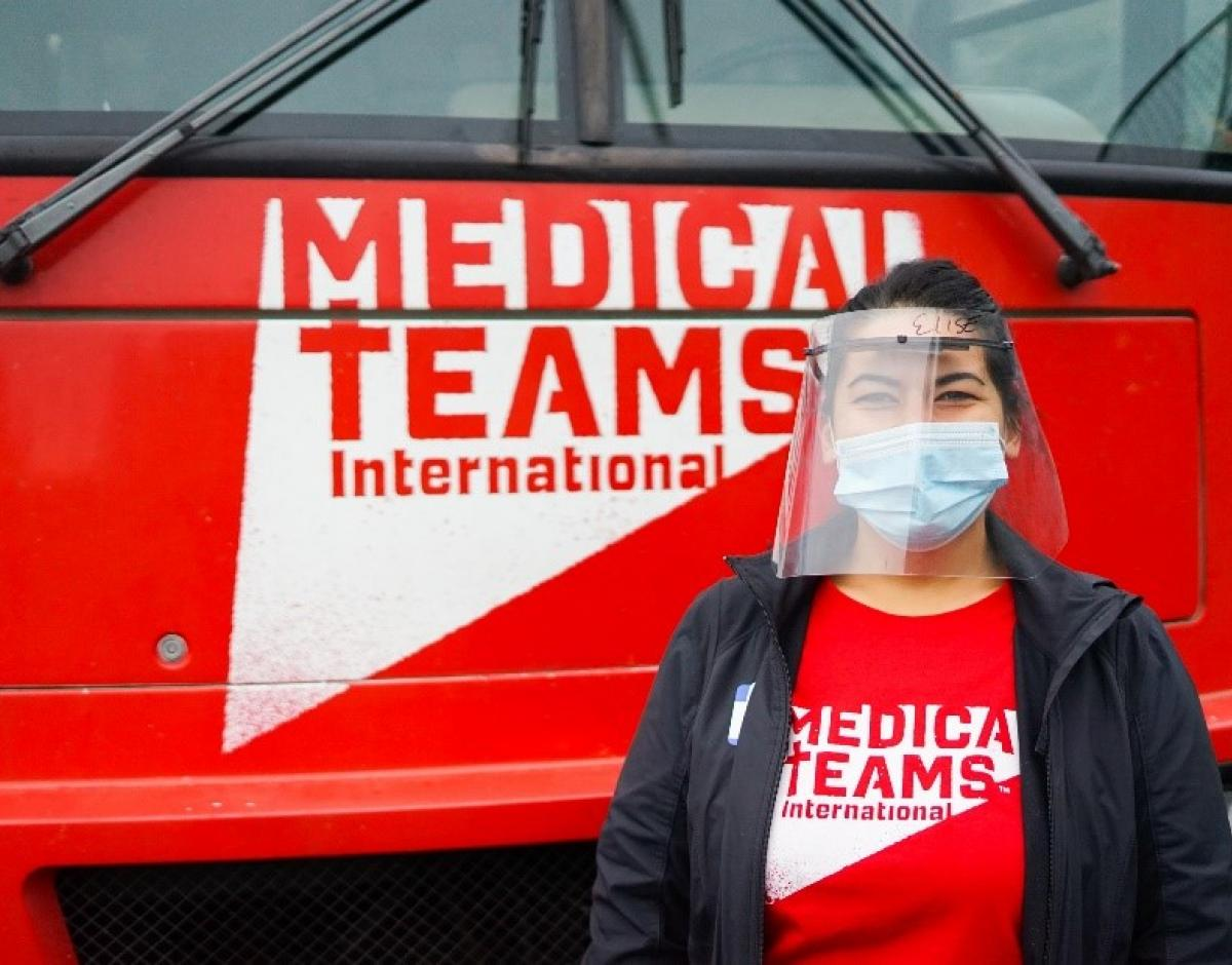 A woman stands in front of a red Medical Teams International vehicle wearing a Medical Teams International shirt. .