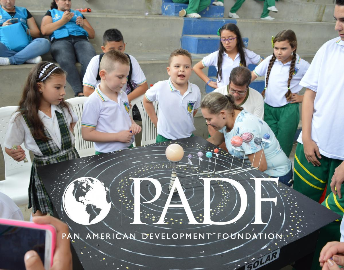A group of school children in Colombia gather around a planetary model. Pan American Development Foundation logo.