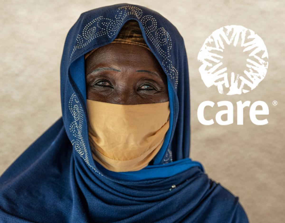 A woman in Niger wearing a headscarf and mask looking forward.