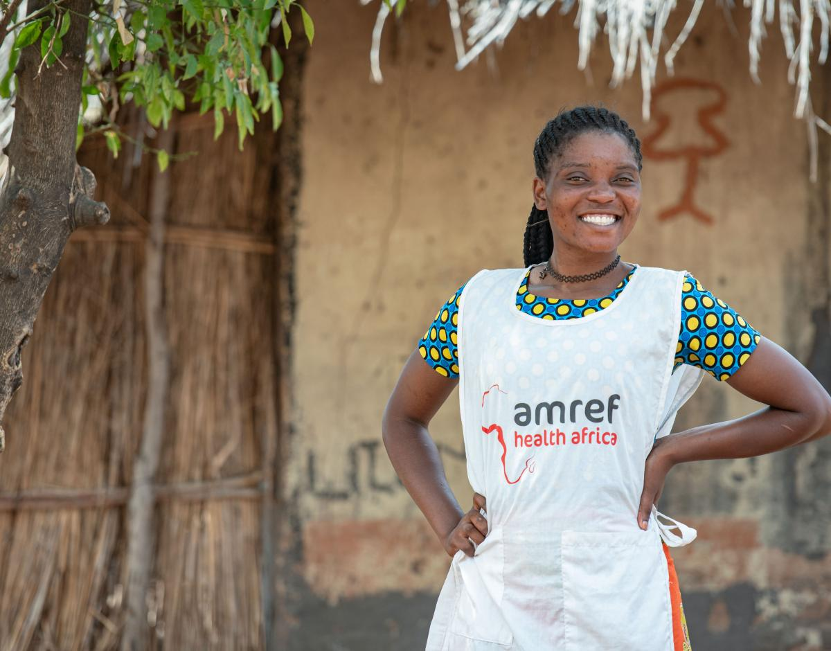 An Amref worked stands smiling with her hands on her hips.