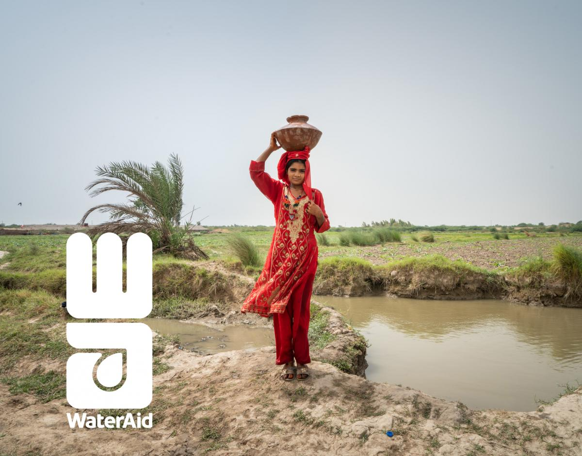A woman carrying a pot of water on her head. WaterAid logo.