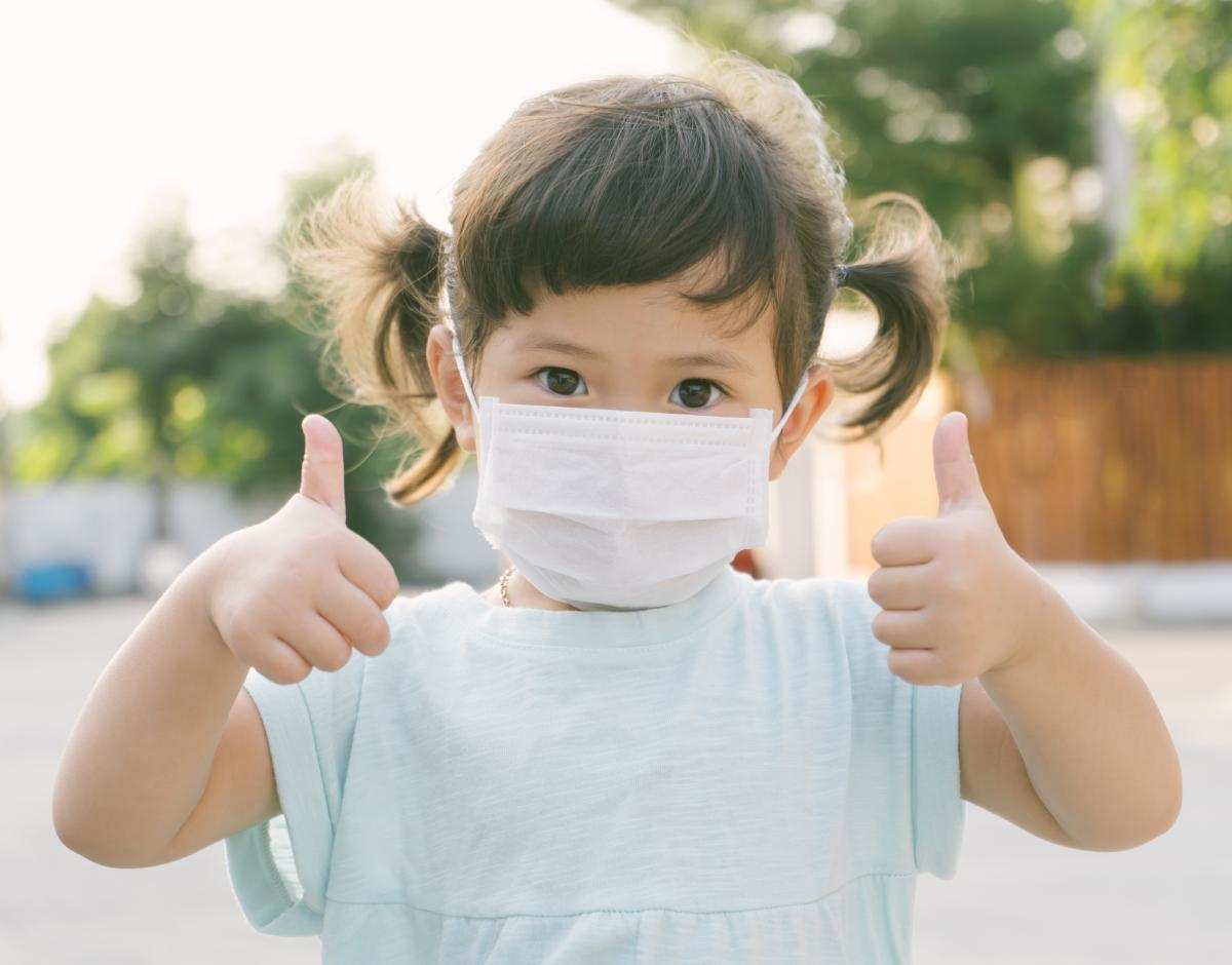 Little Asian girl wearing a mask and giving two thumbs up.