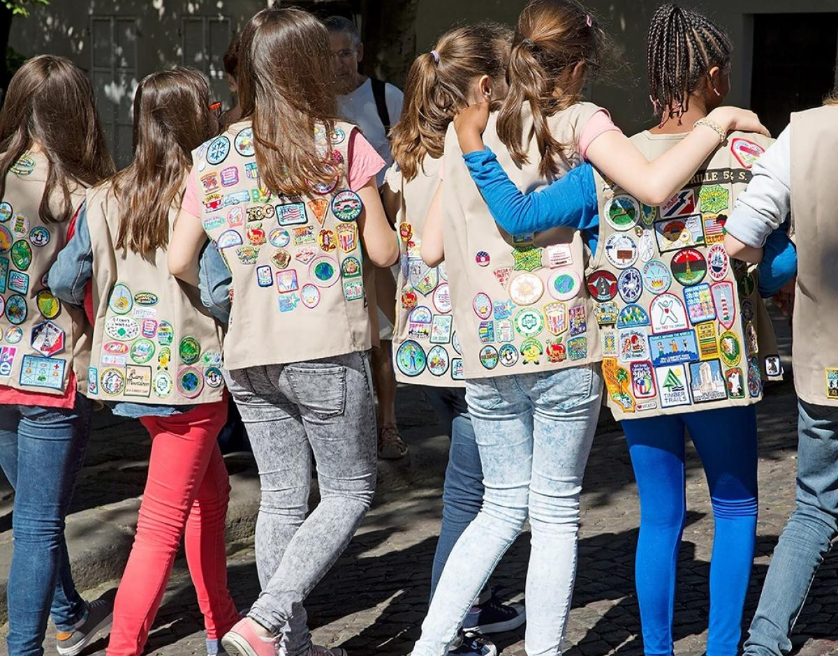 A group of Girl Scouts walking together wearing their vests with their backs to the camera.