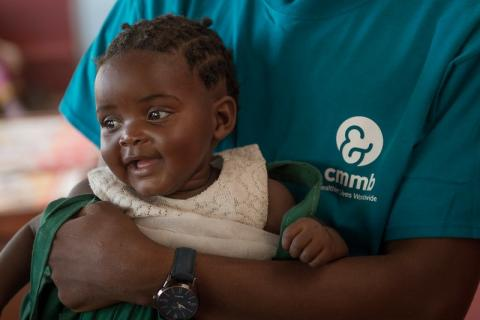 A child being held by a CMMB health care worker.