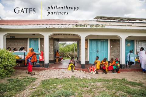 A group of people wait outside of a clinic. Gates Philanthropy Partners logo.