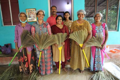 Bindu (center) with a group of women, holding brooms.