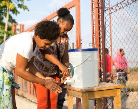 Two women wash their hands at a CMMB handwashing station.