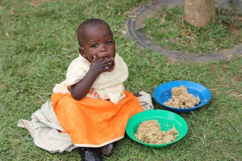 A baby girl sitting on the ground and eating a meal.