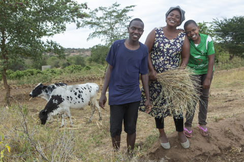 A woman stands with her two children and their cows in Kenya.