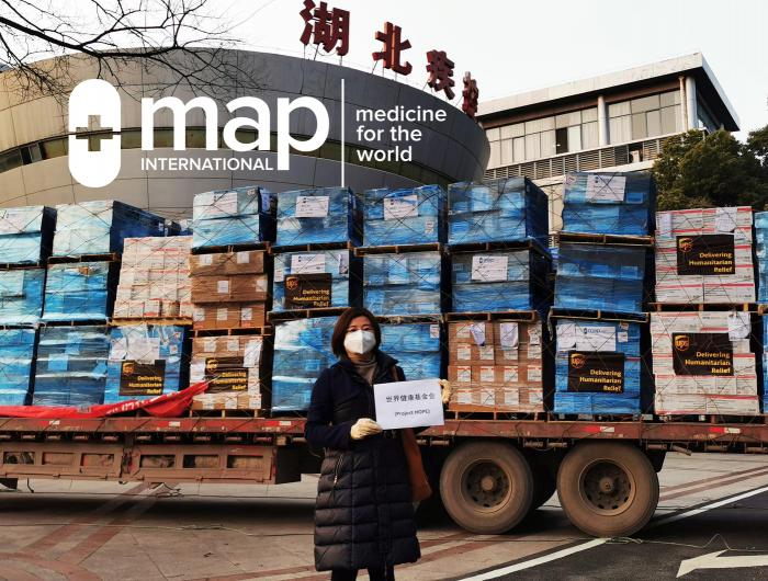 A woman stands holding a Project HOPE sign in front of MAP International supplies shipped by UPS in China.