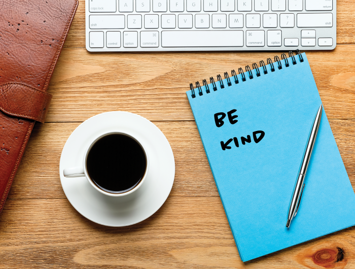"A keyboard, coffee cup and notebook that says ""be kind."""