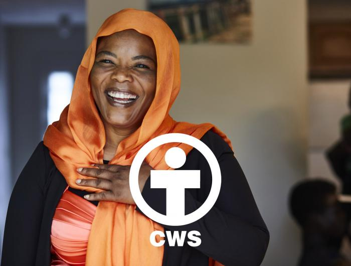 A woman in an orange head scarf smiles at the camera.