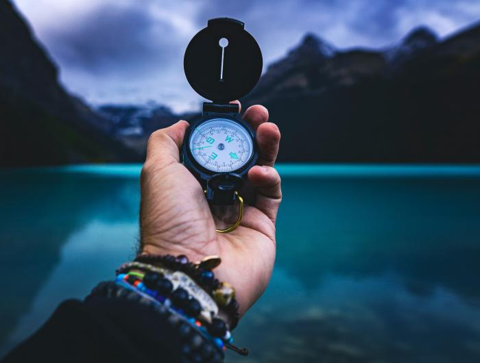 Hand holding a compass in front of a river surrounded by mountains.