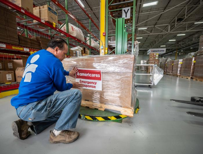 An Americares worker puts an emergency response tag on a shipment of goods in a warehouse.