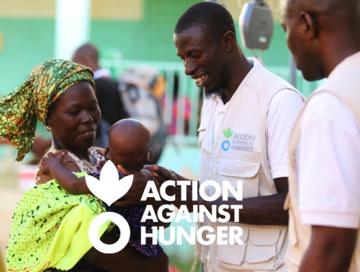 Action Against Hunger staff help woman with baby.