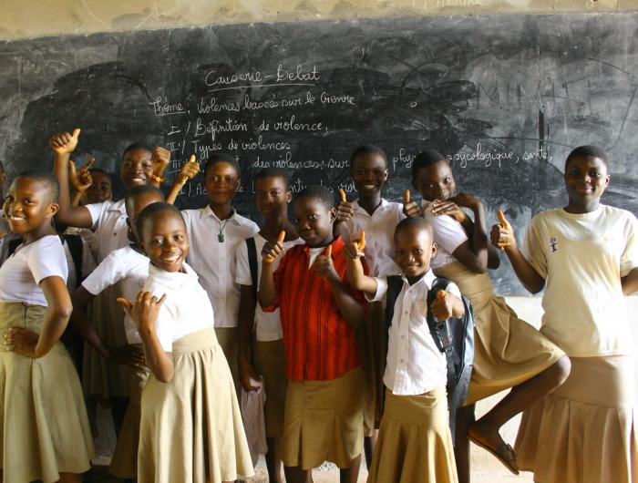A group of students pose in front of a blackboard in their classroom.