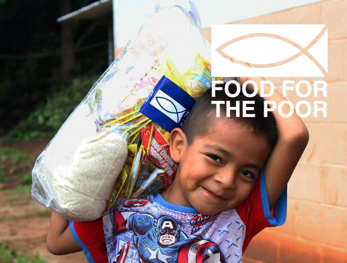 A boy holding a bag of supplies from Food For The Poor.