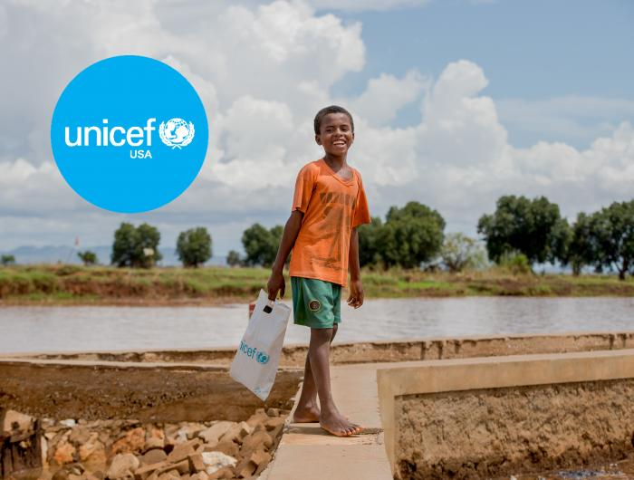 A child walking near a river, holding a UNICEF bag.