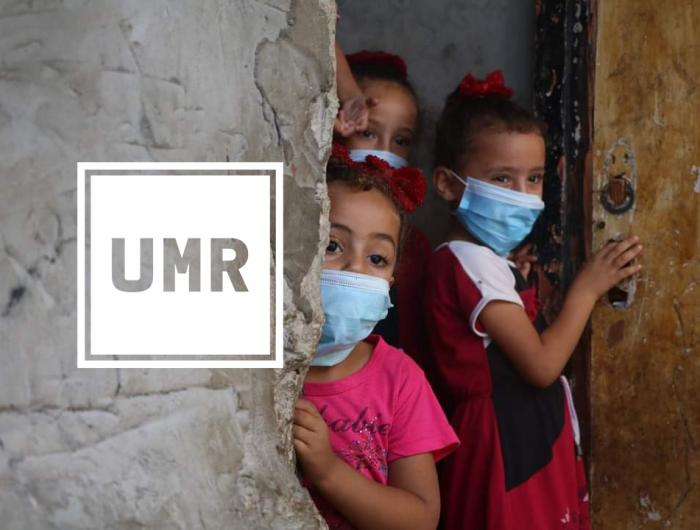 Three children peer around a corner wearing masks. White UMR logo.