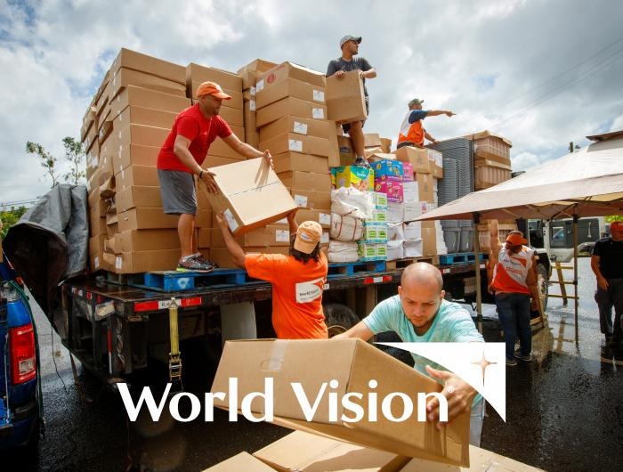 World Vision logo. Image of World Vision volunteers unloading boxes from a truck.