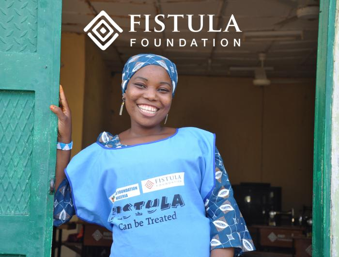 A woman wearing a Fistula Foundation shirt stands in a doorway and smiles.