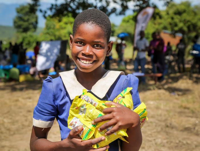 smiling girl holding packs of food