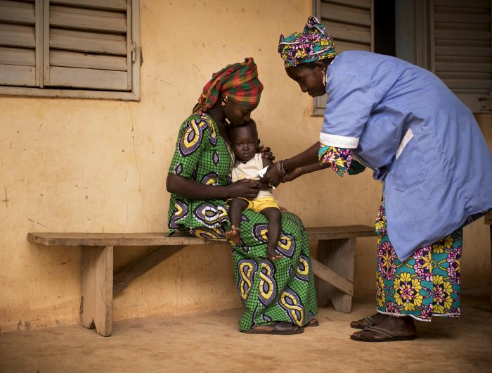 A woman holding her child while they are tested for malnutrition by another woman.