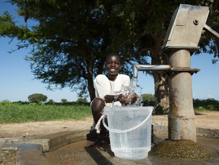 Felister collects water near home in Uganda
