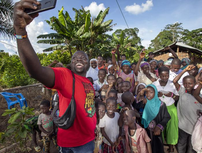 Clement poses with Faustina and her community for a selfie