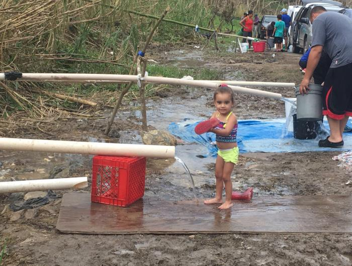A young girl collecting water in Puerto Rico