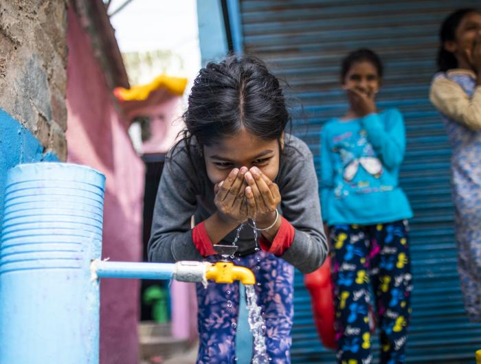 Sneha (10) drinks water from an installed standpost in India