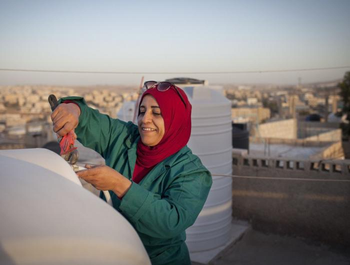Mariam Tawfeeq Matlaq fixes the water tank on her rooftop