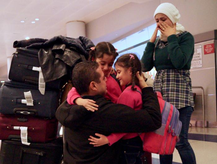 A resettled Syrian family reunites at the airport