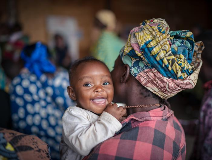 A Baby Smiles From Her Mom's Shoulder, Uganda, 2019.
