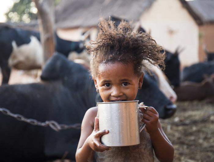 Ravaka drinks clean water outside her home in Madagascar
